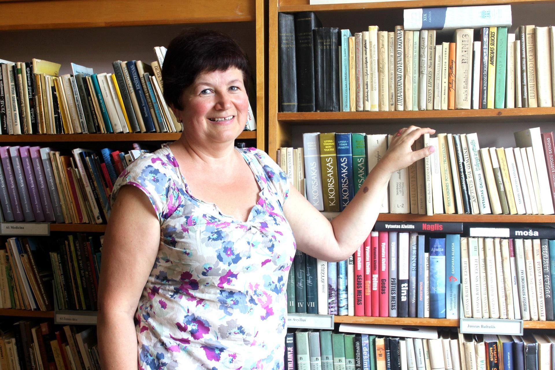 Albina Mačanskienė bibliotekininke Paaluonyje dirba jau 21-erius metus. Moteris knygas ne tik išduoda, tačiau, jei prireikia, nesibodi bibliotekos pasiekti negalinčiam žmogui ir į namus skaitinių nunešti. V. Petrilevičienės nuotr.