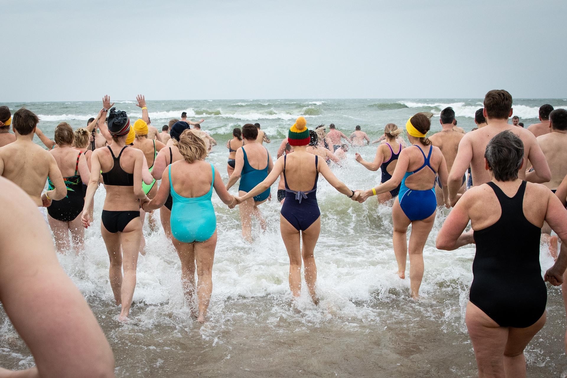 Vienas, du, trys – ir opa vienas po kito į ledines įsisiūbavusias Baltijos jūros bangas! Gintarė Grigėnaitė Photography nuotr.