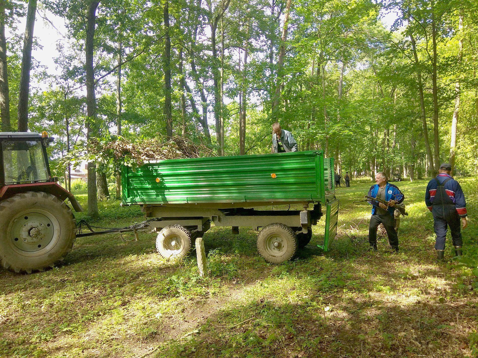 Darbininkai renka parke numestas šiukšles, nukritusias medžių šakas ir šakeles. Viskas kraunama į traktorių ir bus išvežta./ Dimitrijaus Kuprijanovo nuotr.