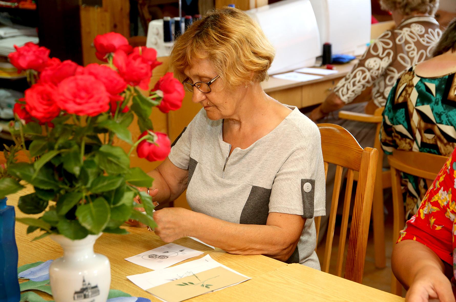 """Mūsų apsilankymo dieną Kėdainių rajono neįgaliųjų draugijos amatų būrelio """"Auksarankės"""" dalyvės simegrafijos (siuvinėjimo ant popieriaus) būdu darė atvirukus."""