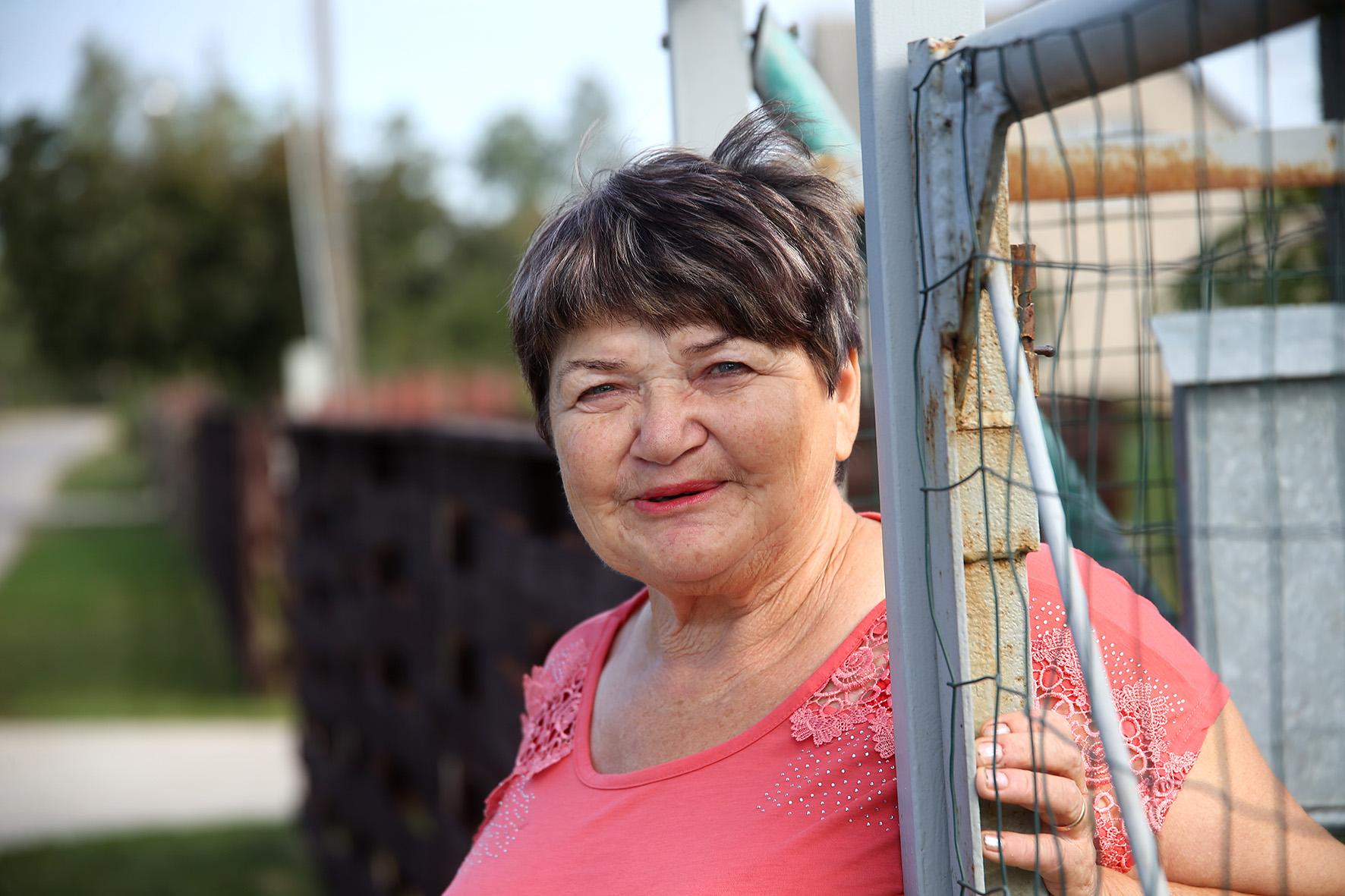 Atvykusius į kaimą mus pasitinka Janina, modama ranka, o kitoje rankoje laikydama milžinišką bulvę. Moters darže šiemet išaugo beveik pusantro kilogramo sverianti bulvė milžinė. A. Barzdžiaus nuotr.