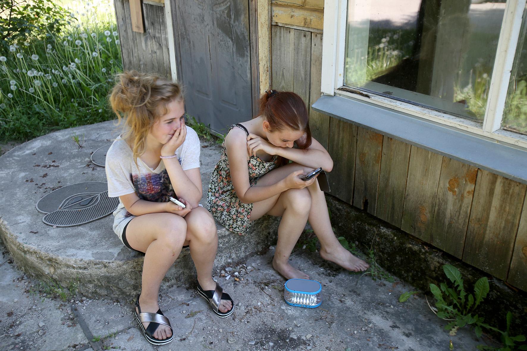 Štai šalia vienos trobos sutinkame sėdinčias Mariją ir Deimantę. Mergaitės klausosi muzikos ir šnekučiuojasi. A. Barzdžiaus nuotr.