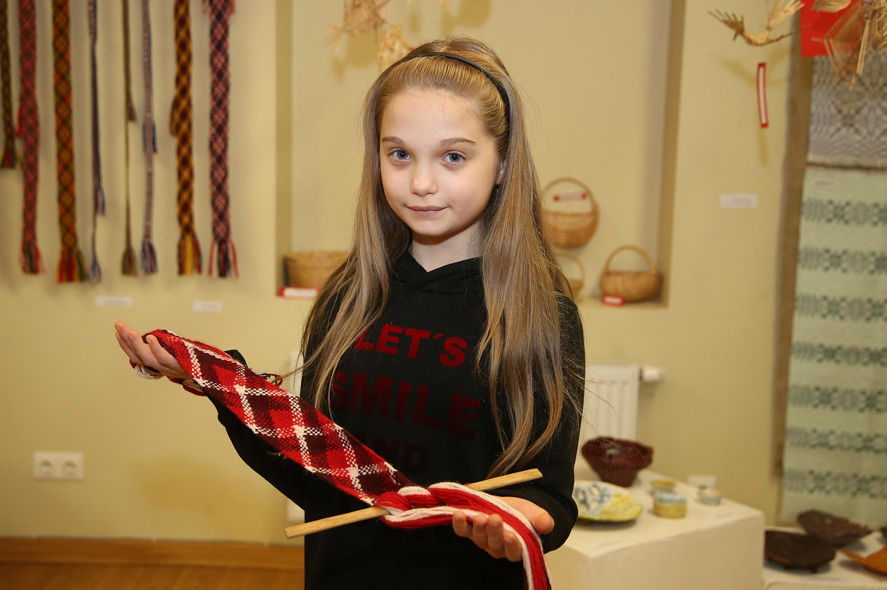 """Laura Steponavičiūtė: """"Su mamos pagalba esu išbandžiusi kurti visų tipų juostas, tačiau labiausiai mėgstu pinti eglines juosteles, apyrankes. Kitokie juostų gaminimo būdai sudėtingesni, jiems reikia daugiau pasiruošimo."""" Algimanto Barzdžiaus nuotr."""