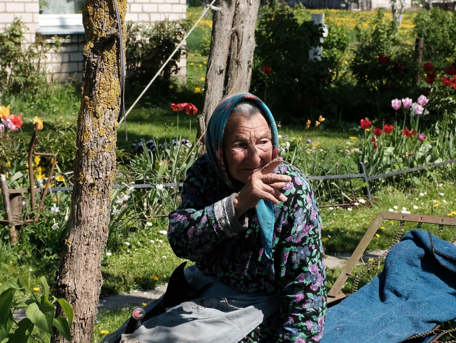 Netoliese pamatome ir močiutę Liubą, kuri sėdi ant suolelio ir mėgaujasi šiltais pavasario saulės spinduliais.  A. Kasparavičiaus nuotr.